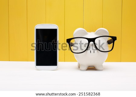 Piggy bank wearing a glasses with a cellphone over yellow wooden wall - stock photo