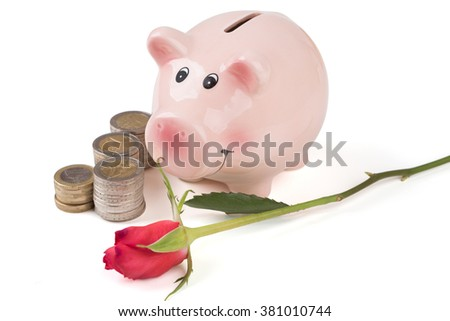 piggy bank with a rose and a stack of coins over white