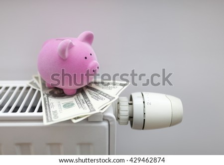 Piggy bank with american dollars on radiator. Energy saving concept. - stock photo