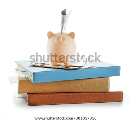Piggy bank with banknote on top of books isolated on white - stock photo