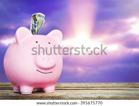 Piggy bank with banknote on wooden table, sunset background - stock photo