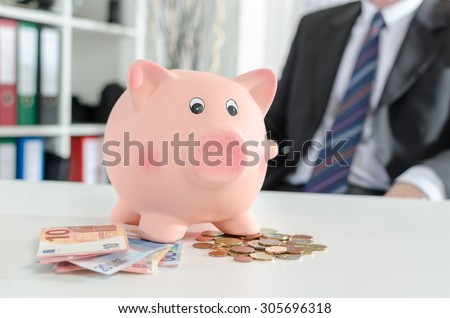 Piggy bank with banknotes and coins on a desk