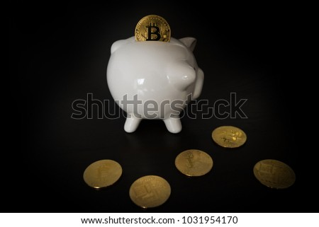 Piggy bank with Bitcoins on dark wooden background. One coin is inserted into the slot however it is to big to pass - concept for the positive value development of the cryptocurrency