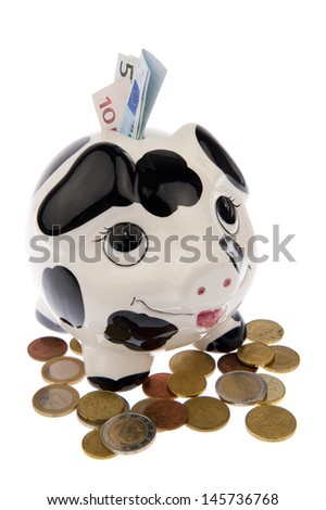 Piggy bank with black and white cow spots, looking upwards and standing in a variety of Euro coins with banknotes in its slot, isolated in white background - stock photo