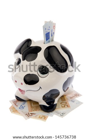 Piggy bank with black and white cow spots, looking upwards in a bed of a variety of Euro banknotes and banknotes in its slot, isolated in white background and viewed from the left - stock photo