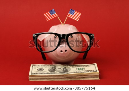 Piggy bank with black spectacle frame of glasses and two small USA flags standing on stack of money american hundred dollar bills on red background - stock photo