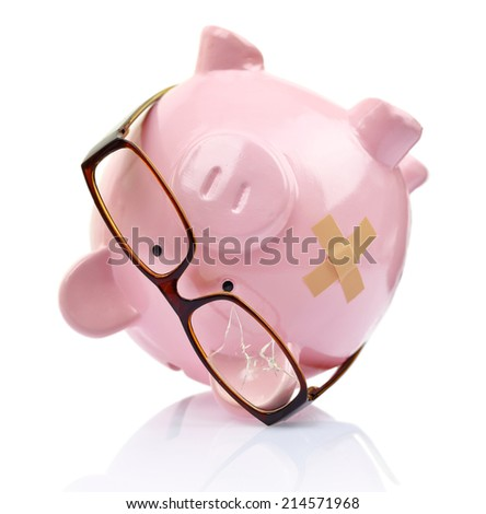 Piggy bank with broken eyeglasses and bandage upside down  - stock photo