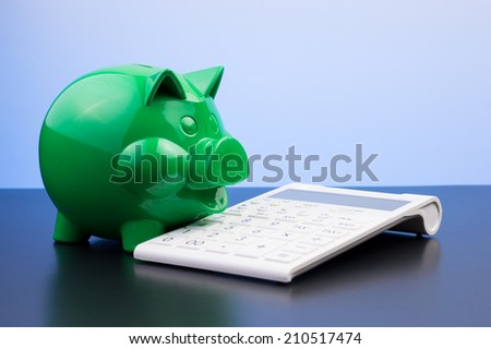 Piggy bank with calculator, focus on tax - stock photo