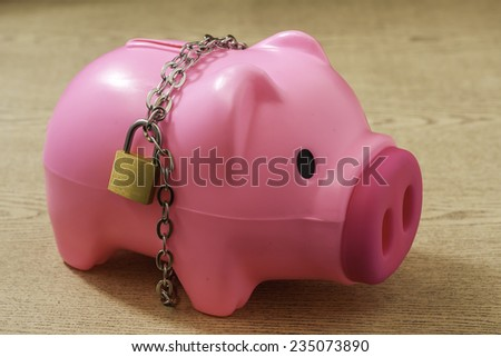 piggy bank with chain lock on wooden background. abstract background for solution to security money saving ,investment ,financial. - stock photo