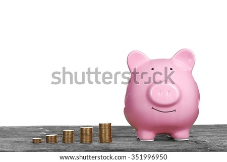 Piggy bank with coins on wooden table, isolated on white