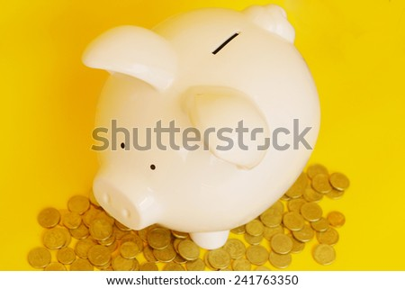 Piggy bank with coins on yellow background - stock photo