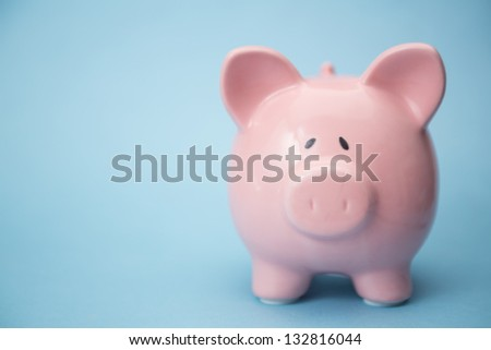 Piggy bank with copy space on blue background - stock photo