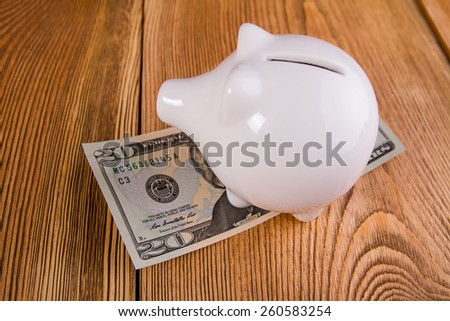 Piggy bank with dolar banknotes - stock photo