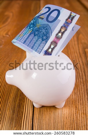 Piggy bank with euro banknotes - stock photo