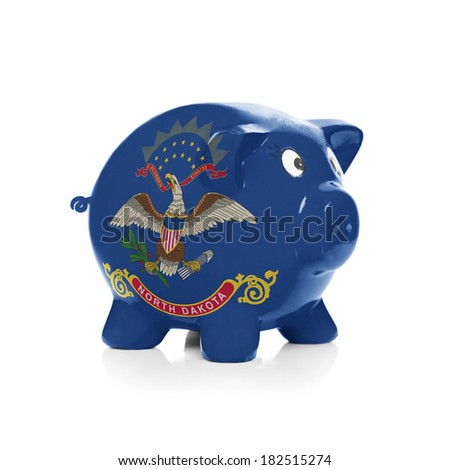 Piggy bank with flag coating over it isolated on white - State of North Dakota - stock photo