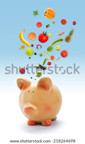Piggy bank with fruits and vegetables - stock photo