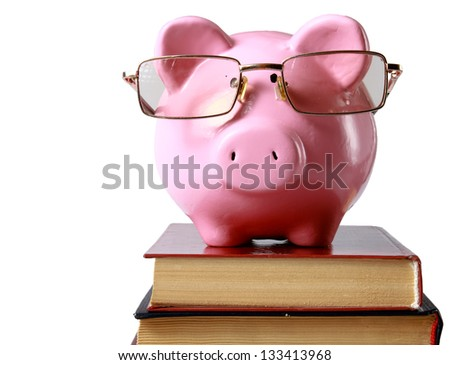 piggy bank with glasses and bookin isolated white background - stock photo