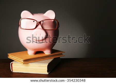 Piggy bank with glasses and books on table ,gray background - stock photo