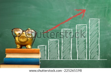 piggy bank with glasses on stack of book over blackboard with graph of success