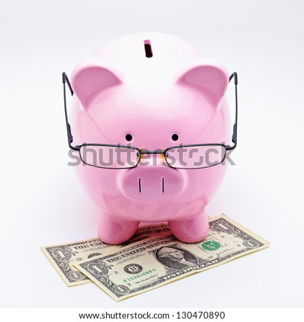 Piggy bank with glasses on U.S. dollars illustrating concepts of money - stock photo