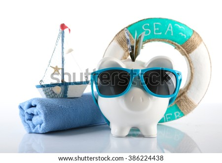 Piggy bank with inserted dollar banknote, towel and sunglasses, isolated on white. Holiday money concept - stock photo
