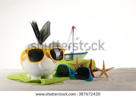 Piggy bank with inserted dollar banknotes, towel and sunglasses on a sand, isolated on white. Holiday money concept - stock photo