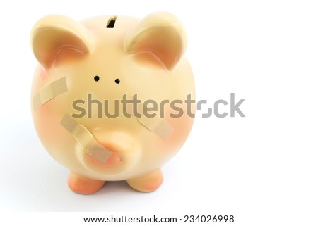 Piggy bank with medical patches, isolated on white background - stock photo