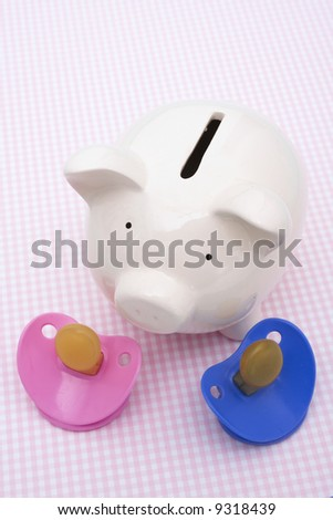 Piggy bank with pacifiers on pink background - stock photo