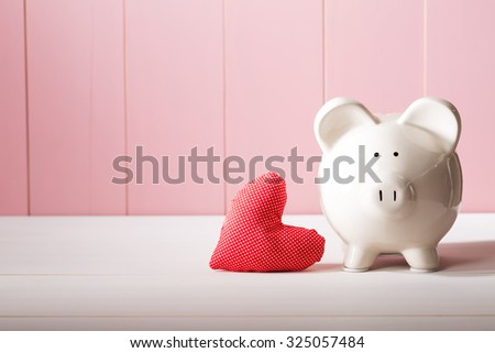 Piggy bank with red heart pillow on pink wooden wall - stock photo