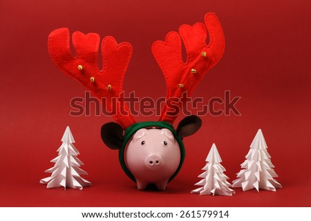 Piggy bank with reindeer horn and jingle bells standing on red background with three white origami trees Christmas background - stock photo