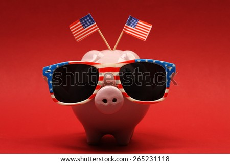Piggy bank with retro sunglasses with USA flag and two small USA flags on red background - stock photo