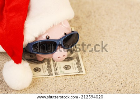 Piggy bank with Santa Claus hat standing on towel from greenback hundred dollars with sunglasses on the beach sand - stock photo