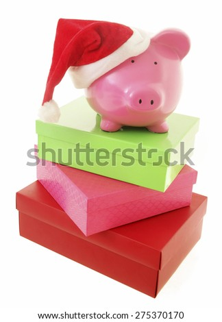 Piggy Bank with Santa hat on white background with gifts - stock photo