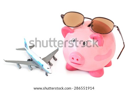 Piggy bank with sunglasses and toy plane on white background - stock photo