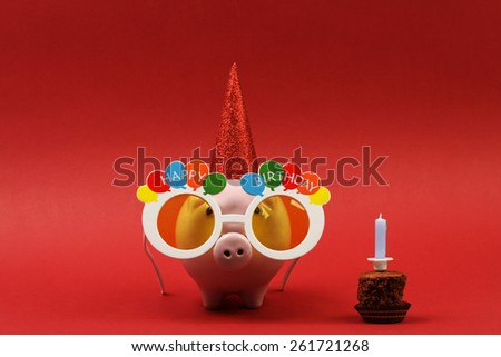 Piggy bank with sunglasses Happy birthday, party hat and birthday cake with blue candle on red background - stock photo