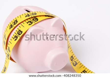 Piggy bank with tape measure - stock photo