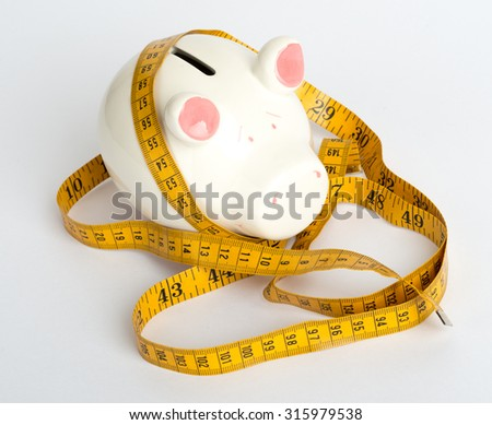 Piggy bank with tape measure on isolated white background, close up view - stock photo