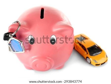Piggy bank with toy car and key isolated on white - stock photo