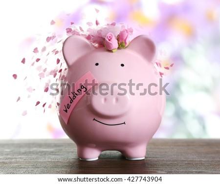 Piggy bank with wedding veil blurred festive background - stock photo