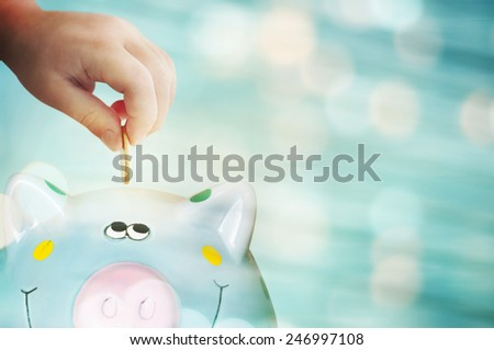 Piggy bank young kid hand - stock photo