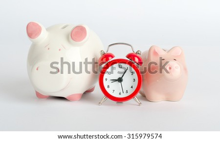 Piggy banks with alarm clock on isolated white background, close up view