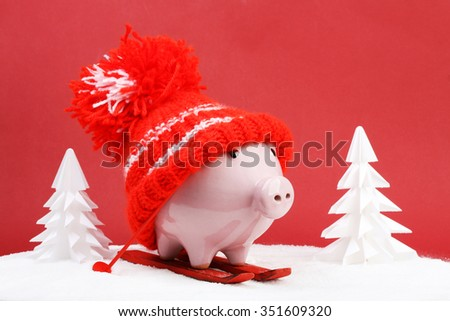 Piggy box with red hat with pompom standing on red ski and ski sticks on snow and around are snowbound trees on red background - stock photo
