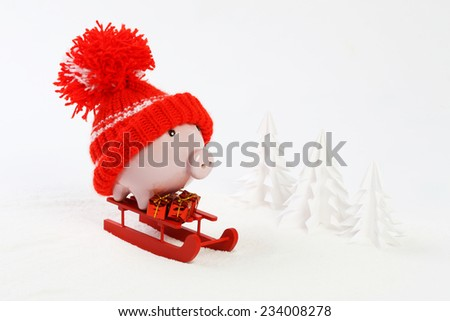 Piggy box with red hat with pompom standing on red sled and holding three gifts with gold bow on snow and around are snowbound trees - stock photo