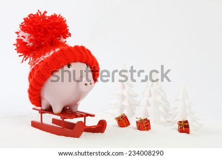 Piggy box with red hat with pompom standing on red sled on snow and around are snowbound trees and three gifts with gold bow - stock photo