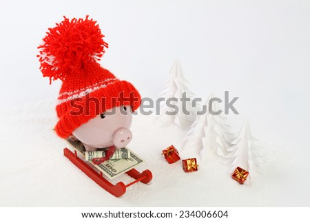 Piggy box with red hat with pompom standing on red sled with blanket from greenback hundred dollars on snow and around are snowbound trees and three gifts with gold bow - stock photo