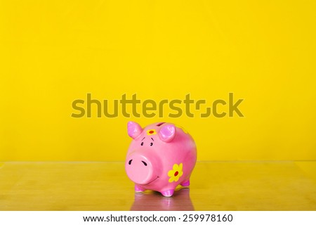 Piggy coin bank on yellow background . Cute white ceramic piggy coin bank. Money savings.Financial security,Personal funds.Spring.