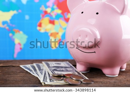 Piggy money box, banknotes and coins on wooden table, close-up - stock photo