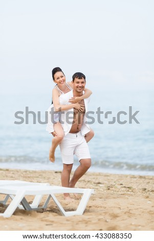 Piggyback. Barefoot young man carrying on shoulders his barefoot girlfriend. They walk on sand along seashore looking at camera smiling - stock photo