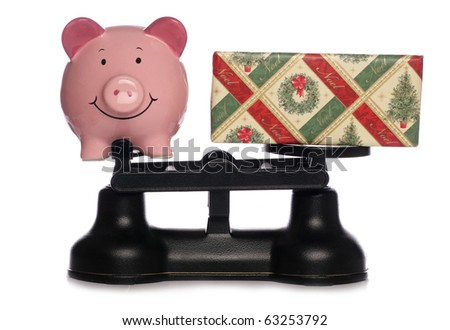 Piggybank and christmas present on scales studio cutout - stock photo