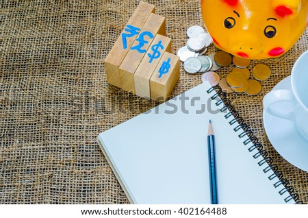 Piggybank and coin, wooden bar graph, pencil on notebook and coffee cup, business time concept - stock photo